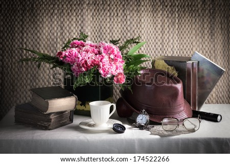 Still life flower vase with vintage objects, books, tea cup, compass, pocket watch, leather hat and old glass on the table