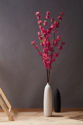 Still life: flowering branches of crimson tea rose in white vase near wooden ladder and empty black vase on the wooden floor. The splendid flowers are outlined against gray wall.