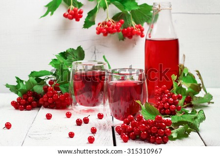 Still life, food and drink, health and homeopathy concept. Viburnum (guelder rose) drink in glass on a wooden table. Selective focus