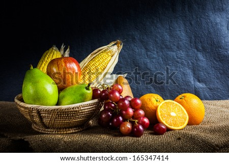 Still life fruits, fresh fruit display in wooden basket and some place on sack cloth