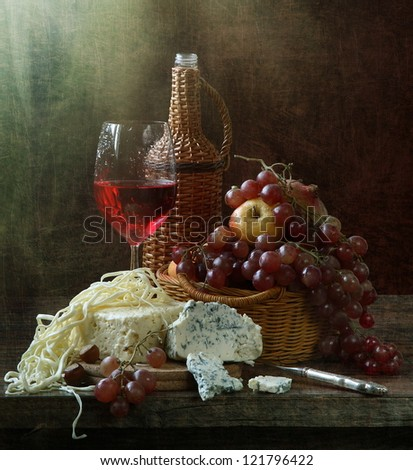 Still-life, glass of fragrant red wine with cheese and juicy ripe fruit