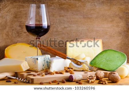 Still life glass of red wine and cheese plate on a vintage wooden background