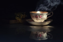 Still life image of  hot tea cup in the dark with Cananga odorata  or Ylang-ylang flower put on old book.Light pass through, shadow touch up the scene.Concept of simple or relax moment with tea.