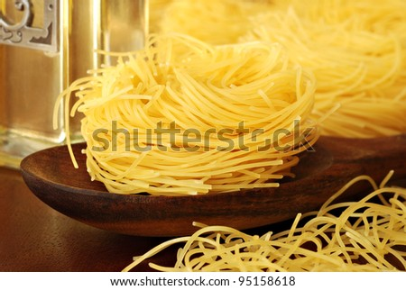 Still life image of pasta nests with wooden spoon and decanter of olive oil.  Macro with shallow dof.