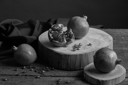 Still life image of Pomegranate and seeds fresh on old wooden plank, blackandwhite