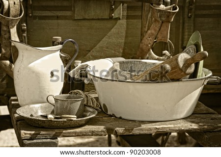 Still life image of vintage cooking utensils and dishes beside an authentic American old west style chuck wagon at an outdoor cooking demonstration (sepia tint added).