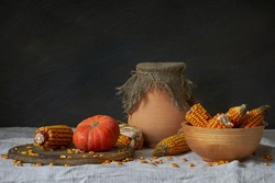 Still life in a rustic style: autumn harvest. Pumpkins and corn on a wooden table. Natural light from a window.