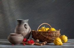 Still life in a rustic style: autumn harvest. Pumpkins and red berries on a wooden table. Natural light from a window.