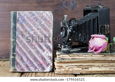 Still life in retro style: vintage photo camera, old books and the dried rose