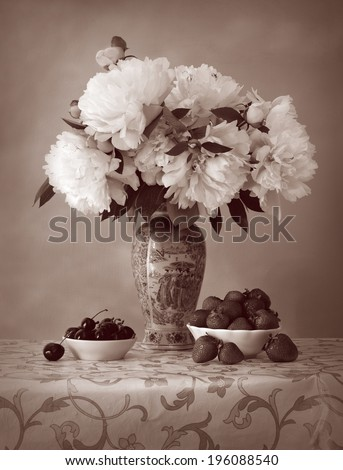 Still Life in style of aged faded photo. Gorgeous white peonies in a porcelain vase with decorative Chinese painting on openwork tablecloth and dishes with sweet strawberries and juicy dark cherries