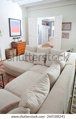 Still life interior design home living room view with a comfortable and welcoming white sofa with cushions, home interior detail. Aspirational and relaxing home family room, indoors living lifestyle.
