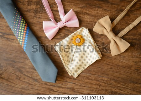 still life men accessories, brown leather shoes, belt, pink bow tie, light brown dotted handkerchief, flower brooch, neck tie, all placing on brown hard wooden floor