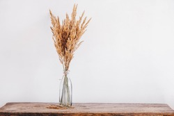 Still life of a bouquet of dried flowers in a glass bottle on a wooden table. Place for text or advertising. View from above