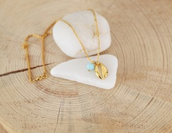 still life of a delicate gold chain necklace with gold shell and turquoise bead
