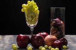 Still life of a glass with grapes, apple, Peach, Plumbs, and a glass of potpourri sitting on wooden table with black background.  Rembrandt lighting inspired