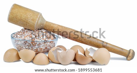Still life of a ground eggshell in a glass bowl, a wooden mortar on a table, isolated on a white background. Stock photo ©