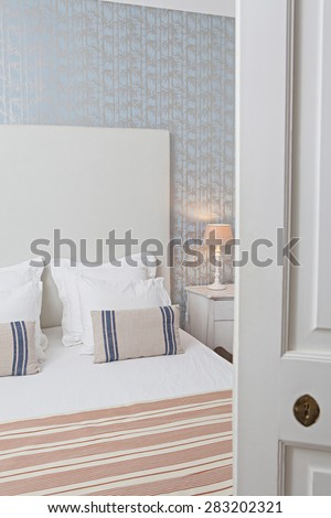 Still life of a luxury home bedroom with stripy furnishings in a quality family home, seen through a door ajar, semi open bedroom door, interior. Aspirational bedroom with pattern wallpaper indoors.