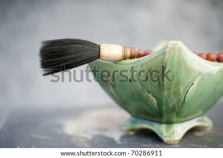 Still life of a traditional chinese calligraphy brush propped on a bowl of stones.