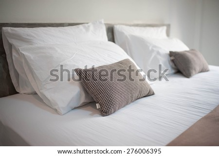 Still life of an empty bed in a hotel bedroom with soft cushions