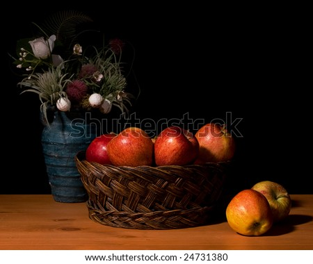 Still life of apples and a vase of silk flowers