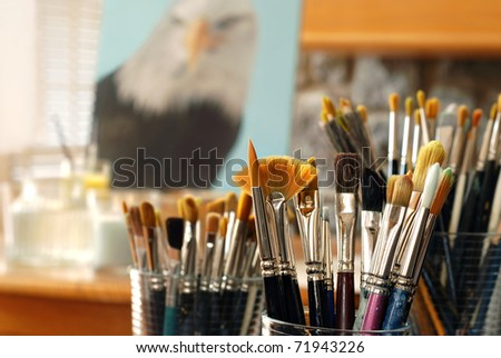 Still life of artist's brushes in sunlit studio with partially completed eagle portrait in background.  (original painting by me) Closeup with extremely shallow dof.