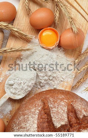 Still life of bread, eggs, cereals, flour and kitchen tools on a wooden board