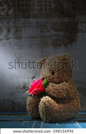 Still life of cute bear doll holding rose bouquet