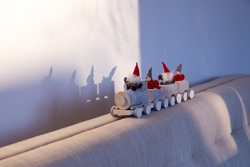 Still life of cute miniature toy elves riding a wooden train on beige linen couch back seen during a sunny sunrise, with their shadow on wall