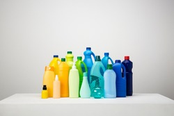Still life of different types of plastic packaging on white and grey set arranged by colours