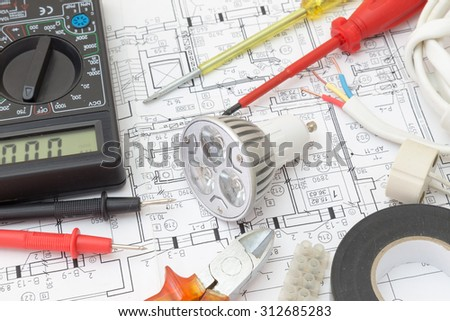 Still Life Of Electrical Components Arranged On Plans. Centered on a light bulb. #312685283