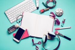 Still life of fashion woman, girl,student on  trendy blue background. Overhead of essentials for modern young person .Note book, nail polish, lipstick,  powder, glasses, watch,  stylish  headphones.