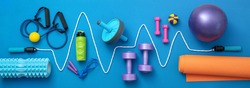 still life of group sports equipment for womens and cardiogram of jump rope, on blue background. Fitness and healthy living, wellness concept.