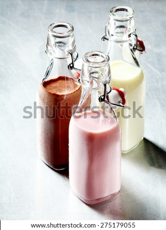 Still Life of Healthy Blended Smoothie Shakes in Three Glass Bottles with Open Tops on Shiny Metal Surface