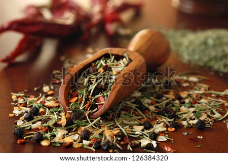 Still life of herbs and spices spilling from small wooden scoop onto wood cutting board with peppers in background.  Macro with shallow dof.  Selective focus on front edge of scoop.