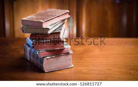 Still life of mysterious looking ancient books in elegant setting.