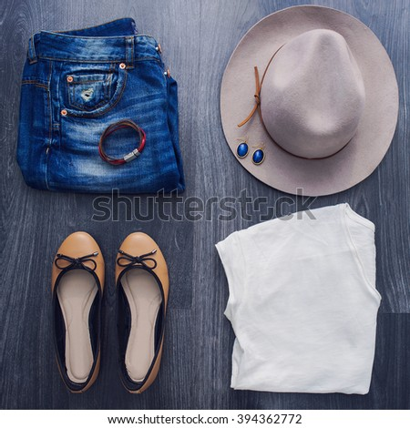 Shutterstock Still Life of Outfit of Women. Casual jeans outfit with hat and white t-shirt on black wooden background.