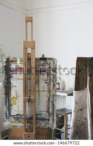 Still life of paint splattered easels in art studio