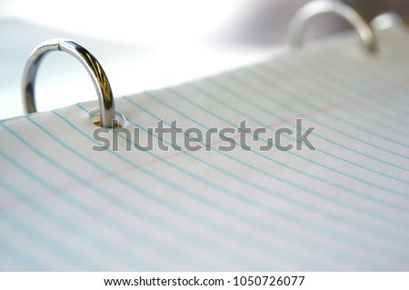 Still life of pen and paper. White college ruled paper with blue lines in a three ring binder. Lined paper in a binder reading to take to school and take notes on. Paper for taking notes on in class.
