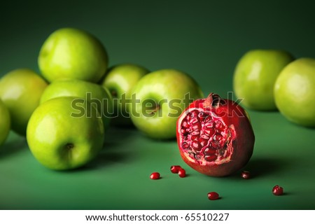 Still-life of pomegranate with green apples on darkly green background, different concepts - red pomegranate before green apples. Color contrast
