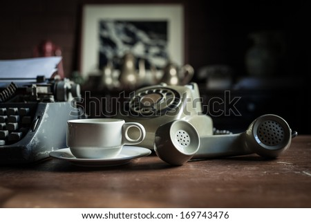 Still life of retro office, telephone, typewriter and coffee cup placed near old lamp on wooden table