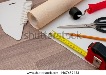 Still life of rolls of wallpaper and different tools for wallpapering. Home repairs.