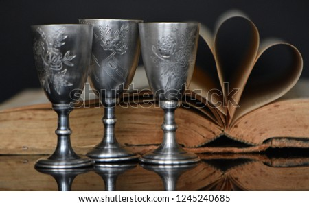 Still life of silver glasses and books. Composition from vintage volume and old silver cups with engraving on glass with bright reflection #1245240685