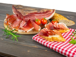 Still life of speck. Bread and slices of speck. Traditional smoked ham from south tyrol. Rustic appetizers.