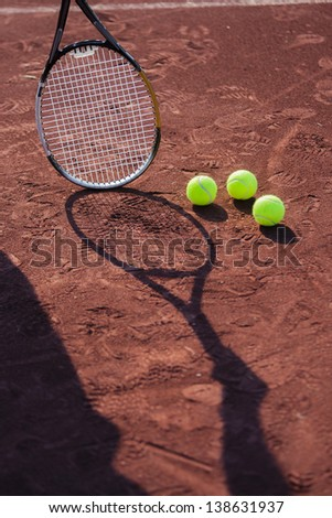Still life of tennis balls and the shadow of a rman holding a tennis racquet on a red clay tennis court.