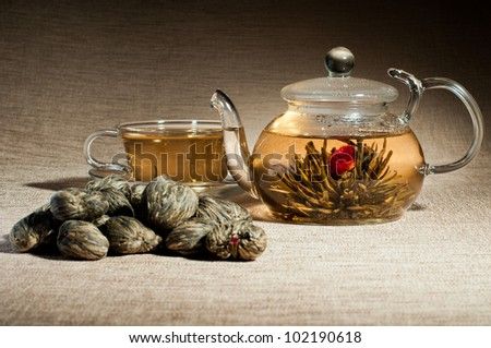 still life of the glass teapot and cup with green tea, on flax-fibre