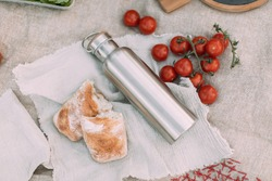 Still life of thermos flask, ciabatta sandwich, tomatoes on tablecloth with wool cover and pillow. Appetizing food served on gray linen tablecloth for autumn picnic in open air.