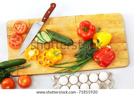 Still life of vegetables and kitchen-knife on cutting board