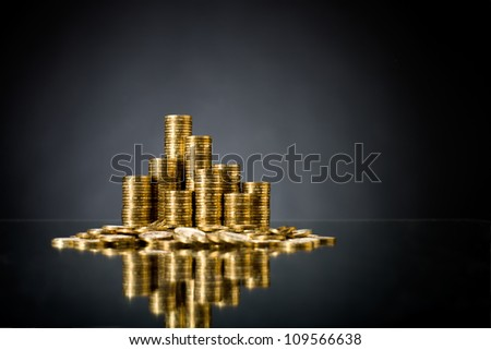 still life of very many rouleau gold  monetary or change coin, on dark blue background