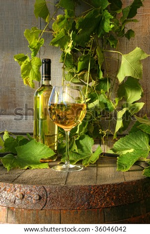 Still life of white wine and grapevine against rustic background