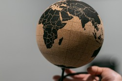 Still life, office design, global map on cork sphere. Eco friendly, sustainable materials. New green deal economy, environmnetal matters. South of the world in one hand.